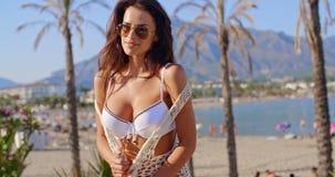 Portrait of Brunette Woman in Bikini on Beach. Waist Up Portrait of Brunette Woman Wearing White Bikini and Sunglasses Standing on Tropical Palm Beach with stock footage