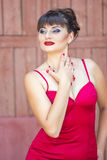 Portrait of a brunette woman with bright makeup. In a skin-tight red dress Royalty Free Stock Images