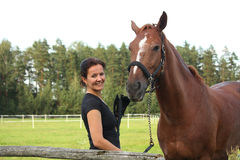 Portrait of brunette woman and brown horse Royalty Free Stock Photography