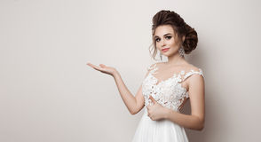 Portrait of brunette woman gesturing super sign by big finger and presenting by hand to side. Bride in wedding dress holding somet Royalty Free Stock Images
