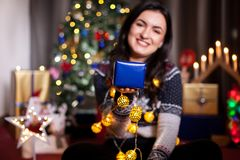 Portrait of brunette woman holding a blue gift box in hands stock photo