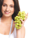 Portrait of a brunette woman holding fresh grapes Stock Image