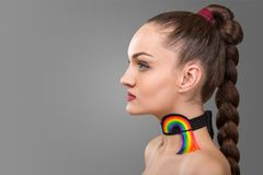 Portrait of brunette woman with long pigtail. decoration on the neck in the form of a rainbow over grey background. Portrait of brunette woman with long pigtail Royalty Free Stock Images