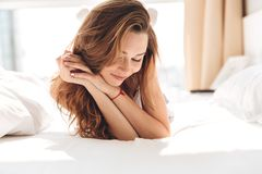 Portrait of brunette woman lying in bed and looking camera. Portrait of brunette carefree woman lying in bed and smiling in the morning Royalty Free Stock Photos