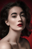 Portrait of brunette woman. Portrait of a brunette woman with professional makeup on red background Royalty Free Stock Photos