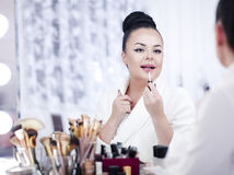 Portrait of a brunette woman putting on make up in front of the mirror Stock Photos