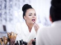 Portrait of a brunette woman putting on make up in front of the mirror Stock Photography