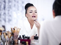 Portrait of a brunette woman putting on make up in front of the mirror Royalty Free Stock Images