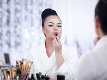 Portrait of a brunette woman putting on make up in front of the mirror Royalty Free Stock Image