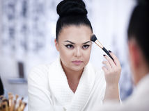 Portrait of a brunette woman putting on make up in front of the mirror Stock Image