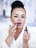 Portrait of a brunette woman putting on make up in front of the mirror Stock Photo