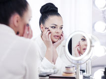 Portrait of a brunette woman putting on make up in front of the mirror Royalty Free Stock Photos