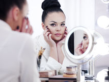 Portrait of a brunette woman putting on make up in front of the mirror Stock Images