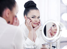 Portrait of a brunette woman putting on make up in front of the mirror Royalty Free Stock Photo