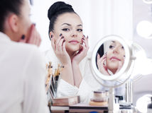 Portrait of a brunette woman putting on make up in front of the mirror Royalty Free Stock Photography