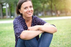 Portrait of brunette woman sitting on the grass Royalty Free Stock Photos