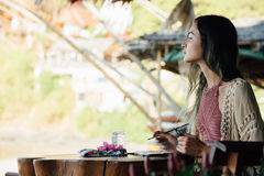 Portrait brunette woman sitting at wooden table and looking into distance. Portrait attractive brunette woman sitting at wooden table in summer cafe and looking stock images