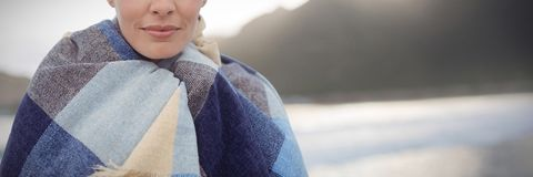 Composite image of portrait of brunette women wearing scarf. Portrait of brunette woman wearing scarf against mountain against sky at beach Stock Photography