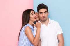 Portrait of brunette woman whispering secret or interesting gossip to excited man in his ear, isolated over colorful background. Portrait of brunette women stock image