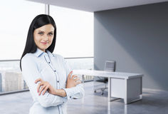 A portrait of a brunette woman in a workplace at modern panoramic office in New York, Manhattan. A concept of financial c Stock Photo