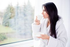 Portrait of a brunette young girl drinking coffee at a hotel room on vacation. She is dreamy and relaxed, looking at the view royalty free stock photo