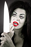 Portrait of a brunette young woman applying lipstick using the k. Nife as a mirror against gray Royalty Free Stock Photos