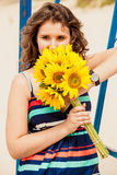 Portrait of brunette young woman holding bunch of yellow flowers Royalty Free Stock Photo