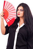 Portrait of a brunette young woman holding red fan royalty free stock photo