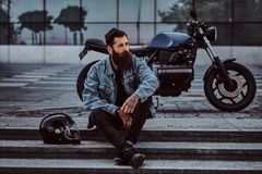Portrait of a brutal bearded male dressed in a jeans jacket sitting on steps near his custom-made retro motorcycle royalty free stock images