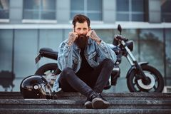 Portrait of a brutal bearded male dressed in a jeans jacket sitting on steps near his custom-made retro motorcycle royalty free stock photography