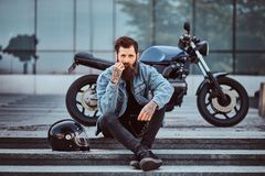 Portrait of a brutal bearded male dressed in a jeans jacket sitting on steps near his custom-made retro motorcycle stock photography