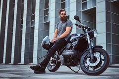 Brutal bearded male in a gray t-shirt and black pants holds a helmet sitting on his custom-made retro motorcycle against. Portrait of a brutal bearded male in a royalty free stock image
