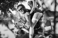 Portrait of brutal biker and beautiful sexy woman on motorcycle Royalty Free Stock Photo
