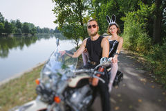 Portrait of brutal biker and sexy girl with motorcycle Royalty Free Stock Photography