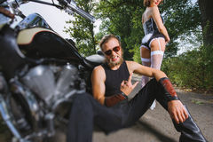 Portrait of brutal biker and sexy girl with motorcycle Royalty Free Stock Image