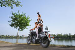 Portrait of brutal biker and sexy girl with motorcycle Royalty Free Stock Photos