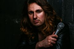 A portrait of a brutal, handsome man, a singer who sits on a chair on a dark background, in a black leather kurt on his royalty free stock image