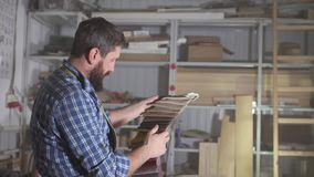 Brutal man in a beard Kraftman chooses a color palette of fabric for making furniture. Portrait brutal man in a beard Kraftman chooses a color palette of fabric stock video footage