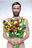 Portrait of brutal man with a bouquet of flowers. Studio photo naked man with a bouquet of tulips Royalty Free Stock Photography