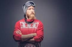 Portrait of a brutal redhead bearded male in a winter hat with protective glasses dressed in a red sweater, posing with stock images