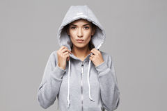 Portrait of brutal sportive girl in hood and sportswear looking at camera over white background. Stock Photography