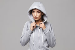 Portrait of brutal sportive girl in hood and sportswear looking at camera over white background. Stock Photos