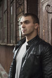 Brutal young man in a leather jacket Stock Photos