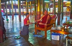 The portrait of Buddist Monk, Ywama, Inle Lake, Myanmar. YWAMA, MYANMAR - FEBRUARY 18, 2018: The smiling Bhikkhu Buddhist monk drinks lemonade  in prayer hall of Stock Photos