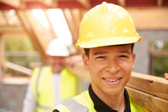 Portrait Of Builder And Apprentice Carrying Wood On Site Stock Images