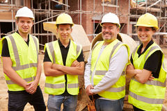 Portrait Of Builder On Building Site With Apprentices Royalty Free Stock Images