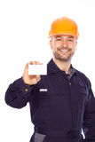 Portrait of the builder with visiting card on a wh Royalty Free Stock Photography