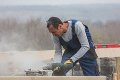 Portrait of builder working with circular saw outdoors, sawdust flying around. Telephoto shot royalty free stock photography