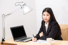 Portrait of business asian woman with laptop writes on a documen Royalty Free Stock Images