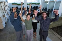 Business colleagues standing with arms up in office. Portrait of business colleagues standing with arms up in office royalty free stock images